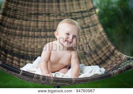 Baby boy with a blanket sitting on the wicker chair