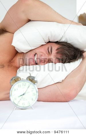 Stressed Man Woken-up By His Alarm Clock Putting His Head Under The Pillow