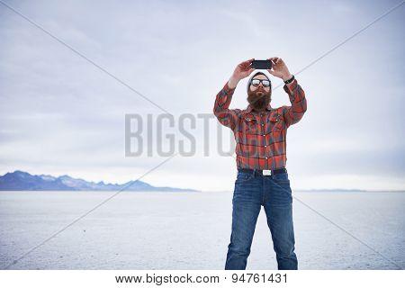 lone lumbersexual hipster taking selfie in salt flats