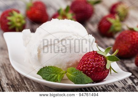 ice cream and strawberries on a wooden table