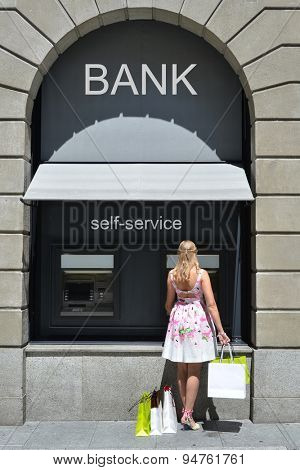 Girl with shopping bags at ATM