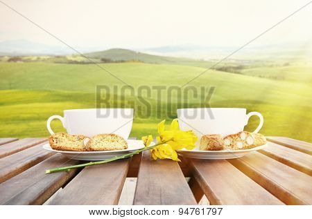 Coffee and cantuccini on the wooden table against Tuscan landscape. Italy