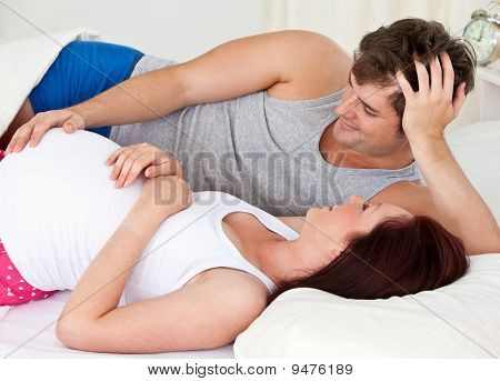 Cute Man Touching The Belly Of His Pregnant Wife Lying On The Bed At Home