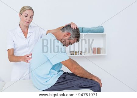 Doctor stretching a man back in medical office