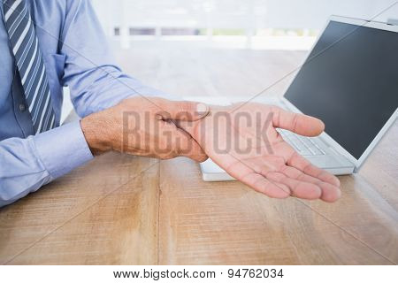 businessman with hand pain in his office
