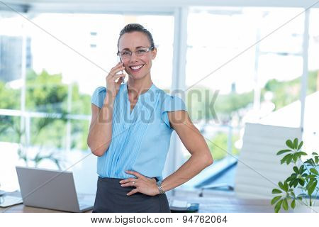 Smiling businesswoman having a phone call in an office