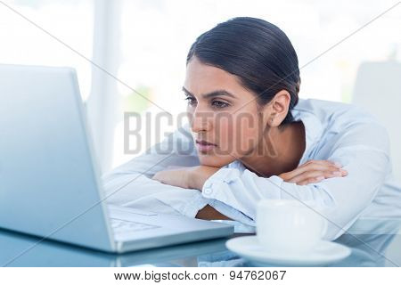 Tired businesswoman looking at her laptop in her office