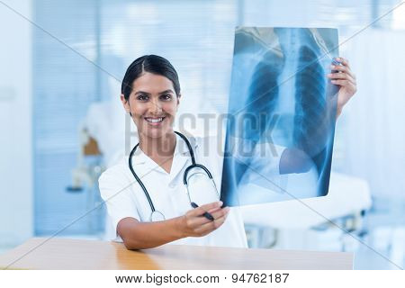 Beautiful smiling doctor analyzing xray in hospital room