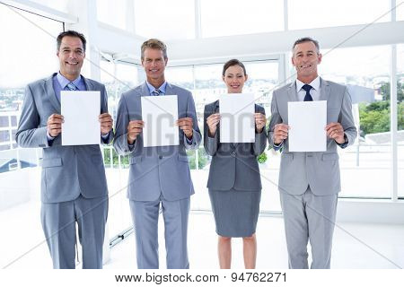 Business colleagues holding sheets of paper together in the office