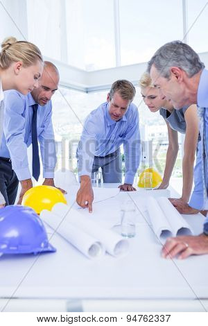 team of business people looking at construction plan in office