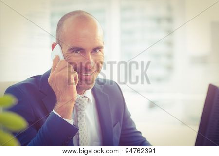 Smiling businessman calling on the phone in the office