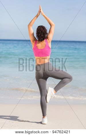 Beautiful fit woman doing yoga beside the sea at the beach