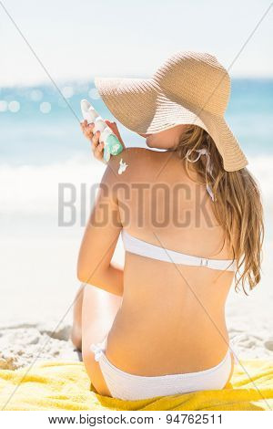 Pretty blonde woman putting sun tan lotion on her shoulder at the beach