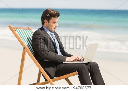 Businessman using his laptop at the beach