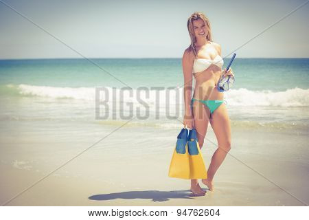 Pretty blonde holding a scuba diving gear on the beach