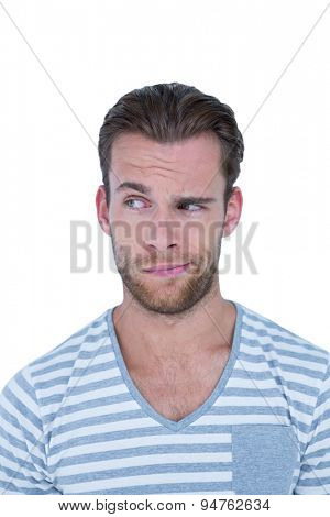 Handsome casual man grimacing in front of camera on white background
