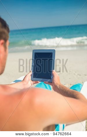 Man using digital tablet on deck chair at the beach on a sunny day