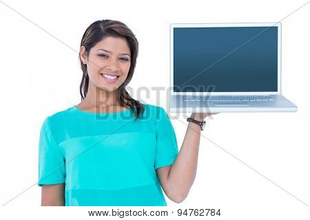 Happy pretty brunette showing laptop computer on white background