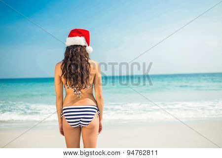 Rear view of pretty brunette in santa hat at the beach on a sunny day