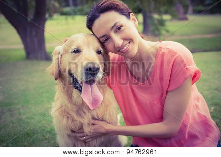 Pretty brunette looking at camera with her dog on a sunny day