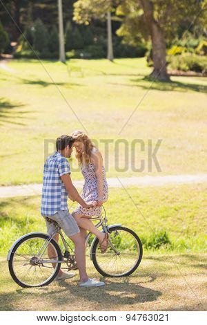 Young couple on a bike ride in the park on a sunny day
