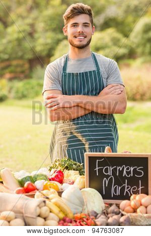 Handsome farmer standing arms crossed on a sunny day