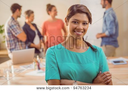 Young casual businesswoman smiling at camera in the office
