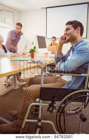 Creative businessman in wheelchair on the phone at office