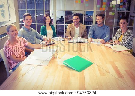 Smiling business people looking at camera during a meeting in the office