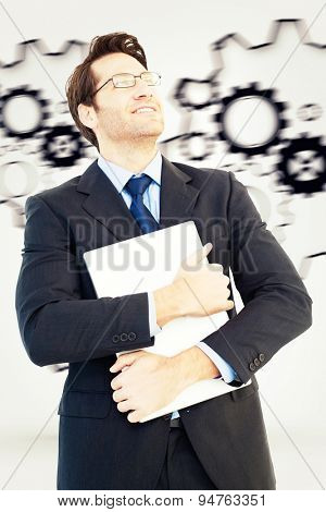 Handsome businessman holding his laptop against turning cogs