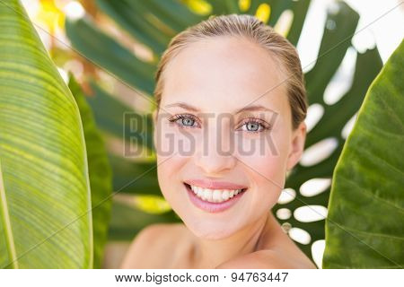 Beautiful blonde smiling at camera behind leaf at the health spa