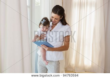 Happy mother with her cute baby girl using tablet at home