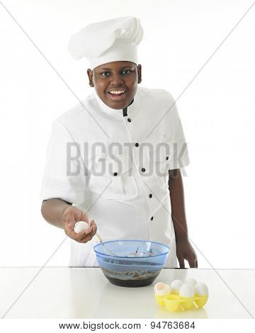 A young chef looking at the viewer as he makes brownie batter with one egg in hand and an empty egg shell nearby.  On a white background.