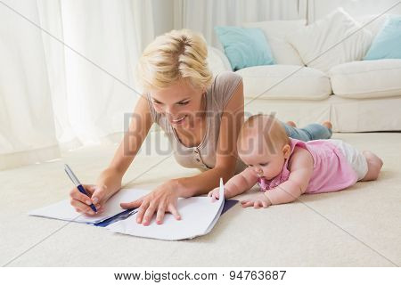 Happy blonde mother with her baby girl writting on a copybook at home in the living room