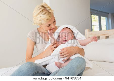 Happy mother with her baby wrapped up in a towel at home in bedroom
