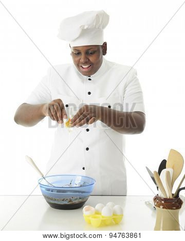 A young chef breaking an egg into the brownie batter he's making.  On a white background.