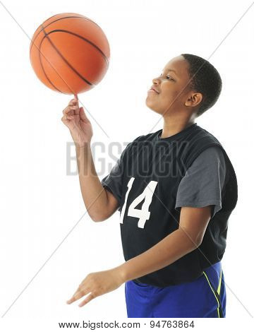 A preteen boy happily spinning his basketball on his index finger.  Motion blur on the ball,  On a white background.