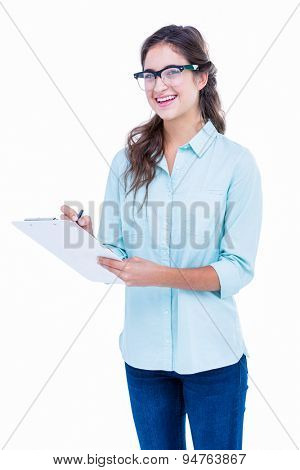 Pretty geeky hipster writing on notebook and smiling at camera on white background