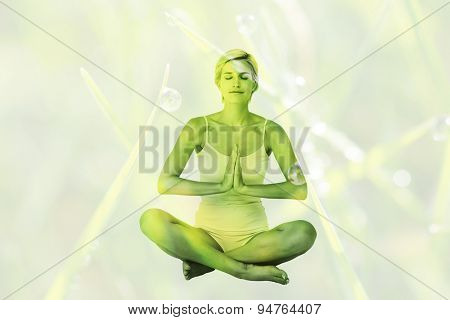 Fit woman doing yoga against dew on the grass