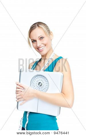 Bright Woman Holding A Scale And A Measuring Tape Smiling At The Camera