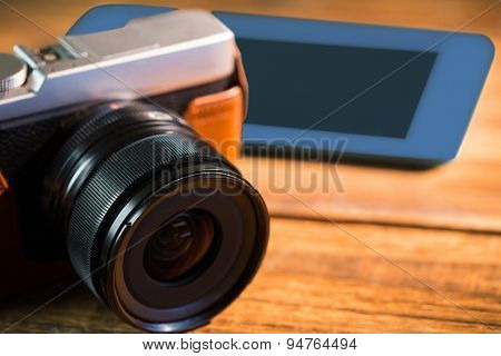 A beautiful brown fashioned camera next smartphone on the wodden table