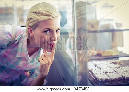 Hesitating pretty woman looking at cup cakes at the bakery