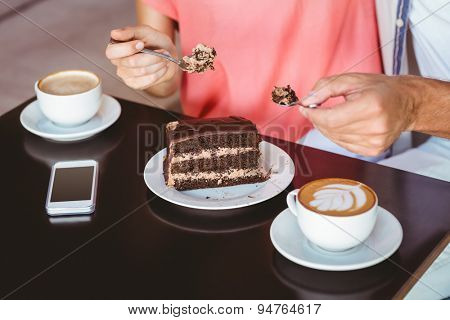 Cute couple on a date sharing a piece of chocolate cake at the cafe