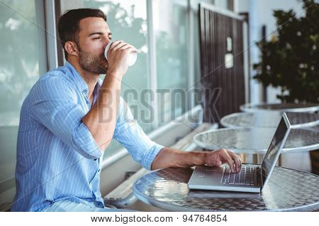 Young businessman drinking coffee beside a laptop outside a cafe