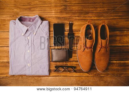 Shirt shoes glasses next to wallet and smartphone on wooden table