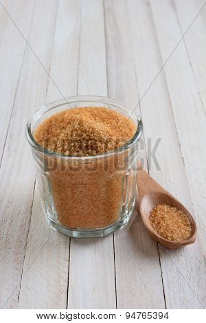 High angle shot of a glass bowl full of granulated brown sugar on a rustic whitewashed wood table. A wood spoon is laying next to the bowl.