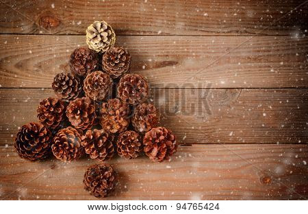 A group of pine cones arranged in a Christmas Tree shape on a rustic wood floor with snow flakes effect. Horizontal format with an instagram retro look and copy space.