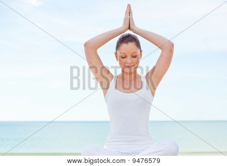 Concentrated Woman Practicing Yoga By The Beach