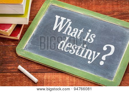 What is destiny question on a slate blackboard with a white chalk and a stack of books against rustic wooden table