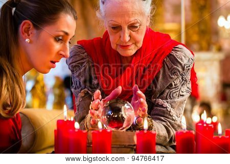 Female Fortuneteller or esoteric Oracle, sees in the future by looking into their crystal ball answering questions from client